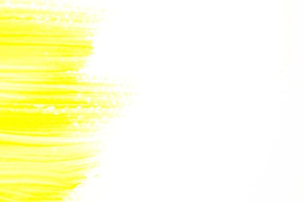 Gelber pinselstrich auf weißem segeltuch