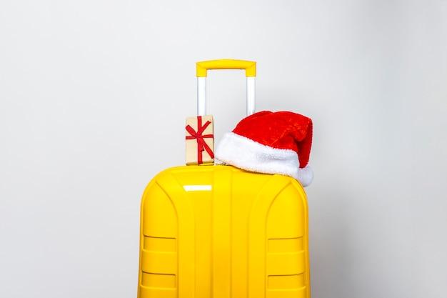 Gelber plastikkoffer, der eine rote weihnachtsmannmütze trägt