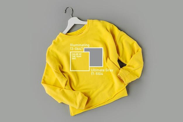 Gelber pullover auf grauem hintergrund. farben des jahres 2021 ultimate grey und illuminating. stilvolle herbst- oder winterkleidung für damen. flache lage, ansicht von oben.