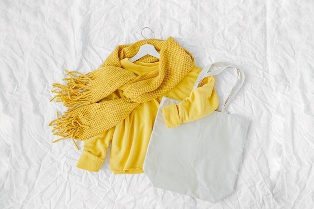 Gelber pullover mit strickschal und tragetasche. herbstmode kleidet collage auf weißem hintergrund. draufsicht flach.
