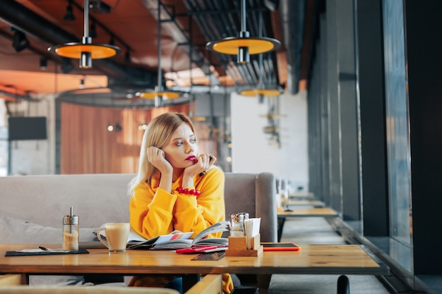 Gelber pullover schöne stilvolle frau mit gelbem pullover und rotem armband, die ins fenster schaut