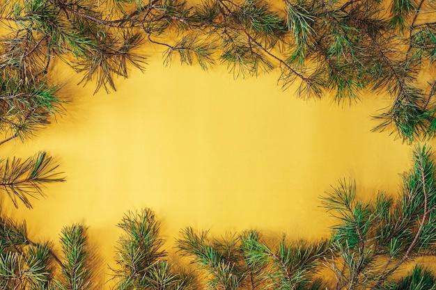 Gelber quadratischer rahmen mit tannenzweigen. weihnachtsdekorationen des neuen jahres. vintage weihnachtsgrußkarte
