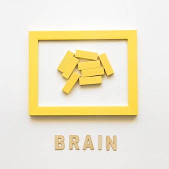 Gelber Rahmen mit Holzklötzen nahe Gehirnwort