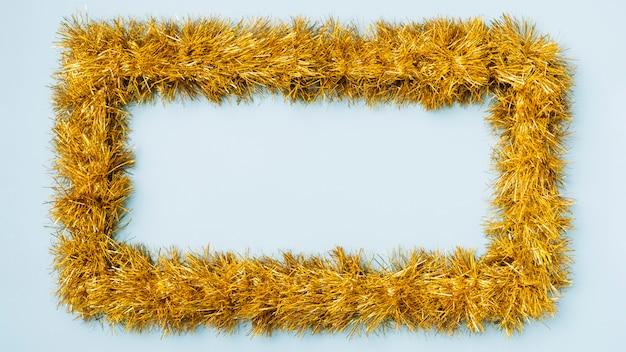 Gelber rahmen vom lametta auf blauer tabelle