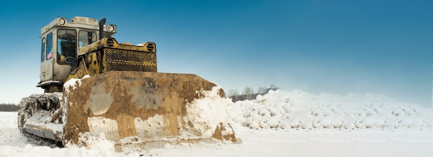 Gelber raupentraktor-bulldozer mit einem eimer arbeitet im winter und räumt die straße vom schnee ab.