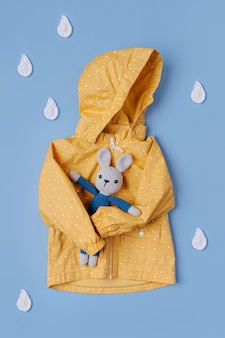 Gelber regenmantel mit spielzeughäschen und dekorativen regentropfen auf blauem hintergrund. herbst-outfit für kinder. herbststimmung
