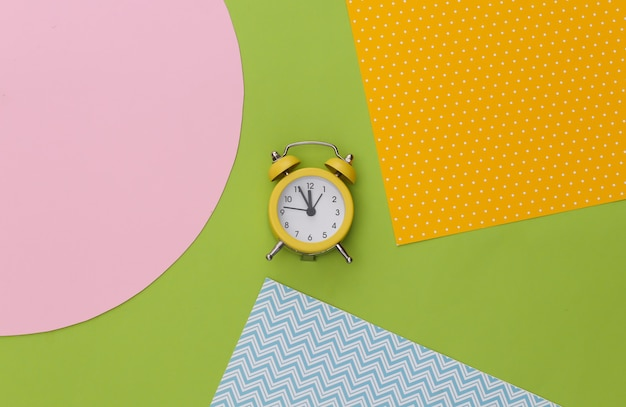 Gelber retro-wecker auf kreativem buntem papierhintergrund. minimalismus