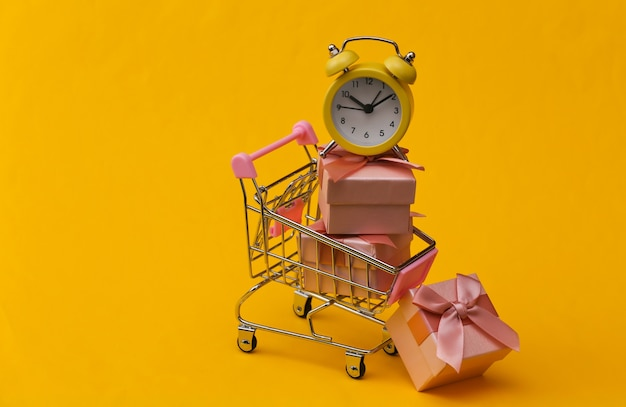 Gelber retro-wecker und stapel geschenkboxen im supermarktwagen auf gelbem hintergrund.