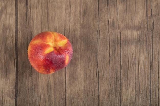 Gelber rötlicher pfirsich auf holzdeck.
