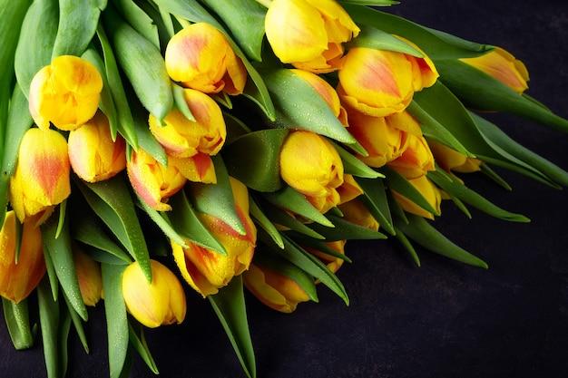 Gelber roter tulpenstrauß der frühlingsblume auf dunklem hintergrund.