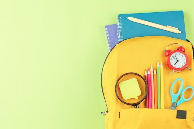 Gelber rucksack mit notizbüchern und studienutensilien