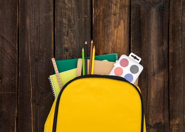 Gelber rucksack mit schulmaterial