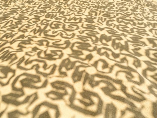 Gelber sandhintergrund des meeresstrandes mit schatten.