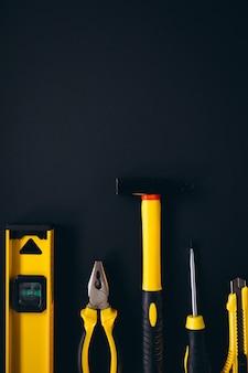 Gelber satz von werkzeugen auf schwarzem hintergrund