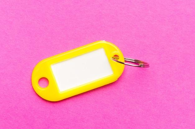 Gelber schlüsselanhänger auf lila pappe strukturiert