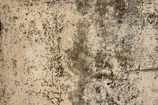 Gelber schmutziger und alter betonmauerbeschaffenheitshintergrund