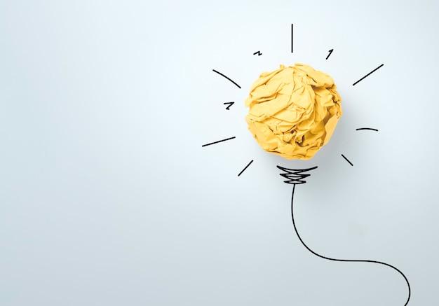 Gelber schrottpapierball mit illustrationsmalerei für virtuelle glühbirne. es ist eine kreative denkidee und ein innovationskonzept.