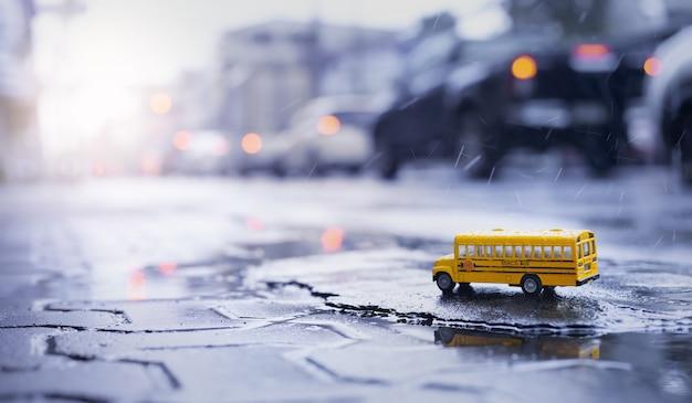 Gelber schulbus (spielzeugmodell) während des harten regenfalls in der stadt, ansicht des niedrigen winkels und der geringen schärfentiefe zusammensetzung. zurück zum schulkonzepthintergrund.