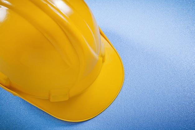 Gelber schutzhelm auf blauem oberflächenkonstruktionskonzept.