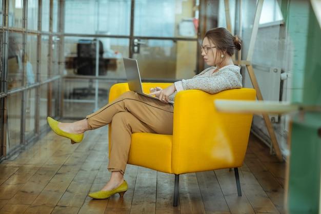 Gelber sessel. dunkelhaarige, stilvolle geschäftsfrau, die in einem schönen bequemen gelben sessel sitzt sitting