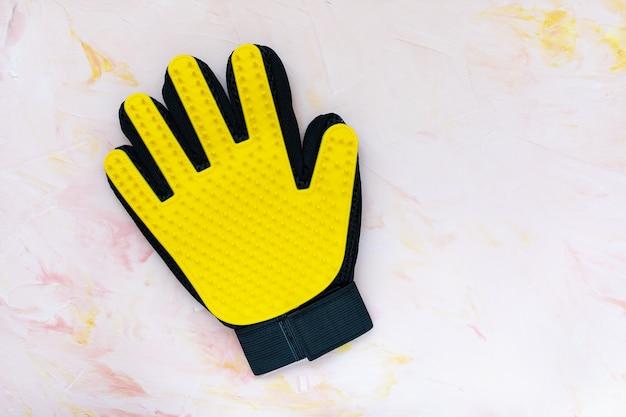 Gelber silikonhandschuh für katzen und hunde, die auf rosa wand pflegen, kopieren raum. haustierpflege, handmassage, reinigung und bürsten haustiere konzept