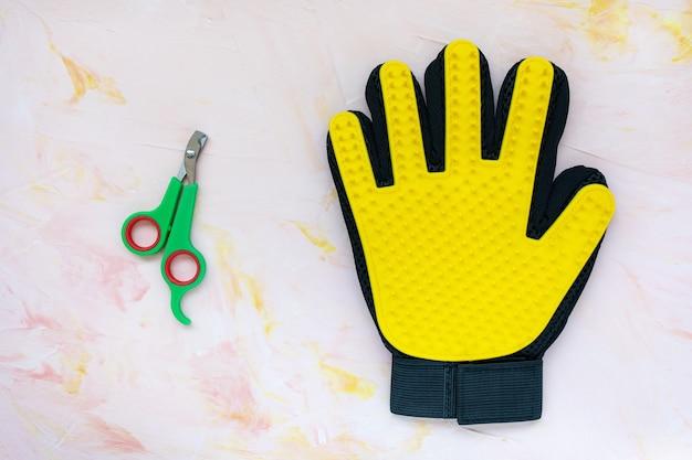 Gelber silikonhandschuh und nagelknipser für katzen und hunde