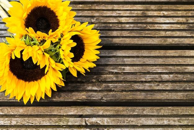 Gelber sonnenblumenblumenstrauß auf hölzernem rustikalem hintergrund