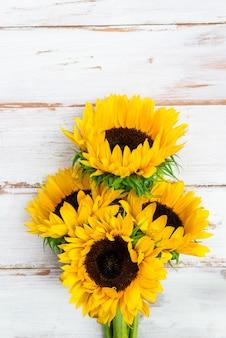 Gelber sonnenblumenblumenstrauß auf weißem rustikalem hintergrund