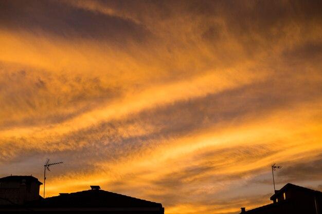 Gelber sonnenuntergang über blauem himmel. silhouette der häuser am horizont