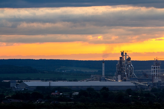 Gelber sonnenuntergang über industrielandschaft mit fabrikkaminen und rohren mit dem rauche, der die atmosphäre verunreinigt.