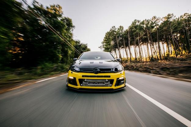 Gelber sportwagen mit schwarzem autotuning auf der autobahn. vorderansicht.