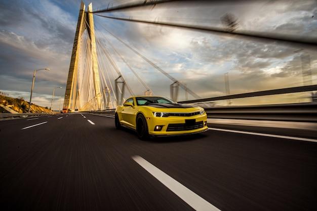 Gelber sportwagen mit schwarzem autotuning auf der brücke.