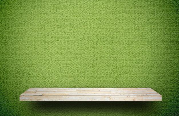 Gelber steinfelsenregalzähler auf grünem teppich für produktanzeige