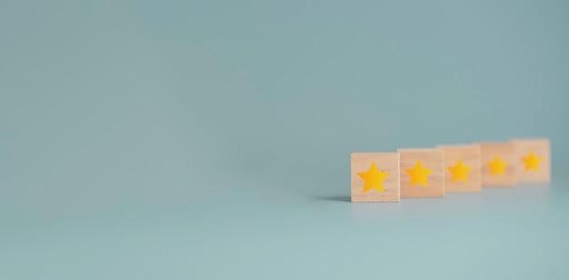 Gelber sterndruckbildschirm auf hölzernem würfelblock mit blauem hintergrund