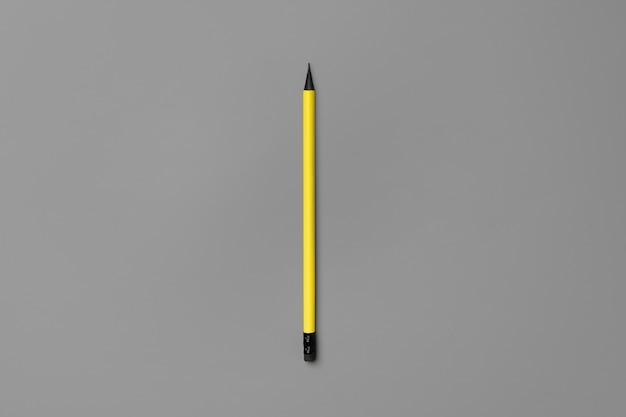 Gelber stift auf grauer hintergrundoberansicht