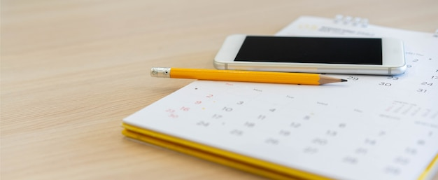 Gelber stift mit smartphone auf kalender am home-office-tisch für terminkonzept