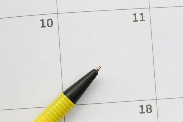 Gelber stift wird am 11. tag auf den kalender gelegt und hat kopienraum.