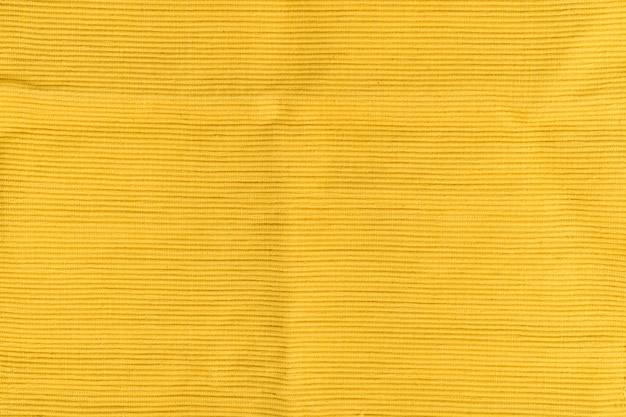 Gelber strukturierter baumwollstoff. gerippte textur. fester nahtloser hintergrund.