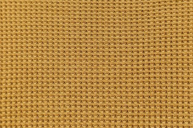 Gelber strukturierter stoffmusterhintergrund für entwurf