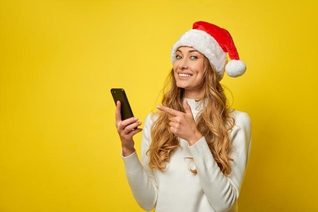 Gelber studiohintergrund des weihnachtsmann-weihnachtsmanns der frau mit smartphone in der hand