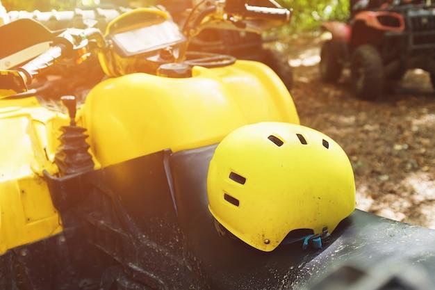 Gelber sturzhelm auf einem atv im wald, im schlamm. räder und elemente von geländefahrzeugen in schlamm und lehm
