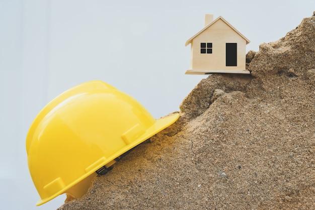 Gelber sturzhelm und hölzernes musterhaus auf einem sandhaufen