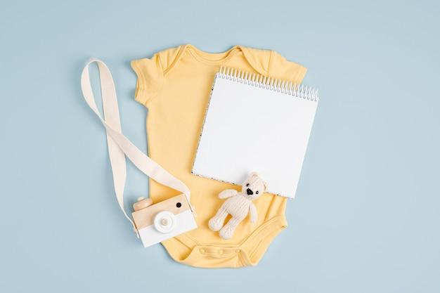 Gelber süßer babybody mit mock-up-karte. set kinderkleidung und accessoires. mode neugeborenes. flache lage, ansicht von oben