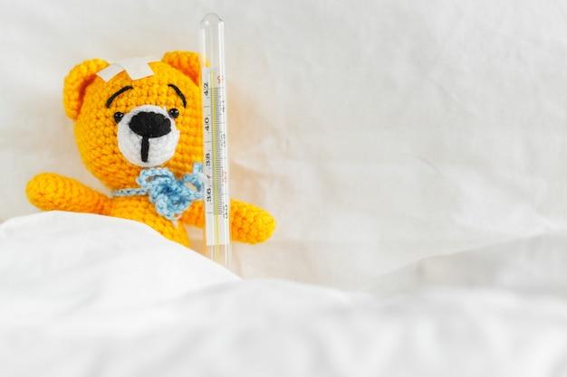 Gelber teddybär mit thermometer und gips auf kopf im weißen schlafzimmer.