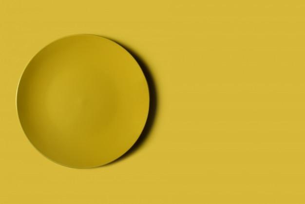 Gelber teller auf einem gelben backgroung.