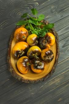 Gelber tomaten goldener holzapfel auf hölzernem hintergrund.