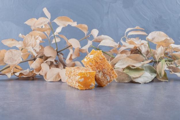 Gelber traditioneller türkischer genuss mit erdnüssen auf grauem hintergrund mit dekorativen trockenen blättern.