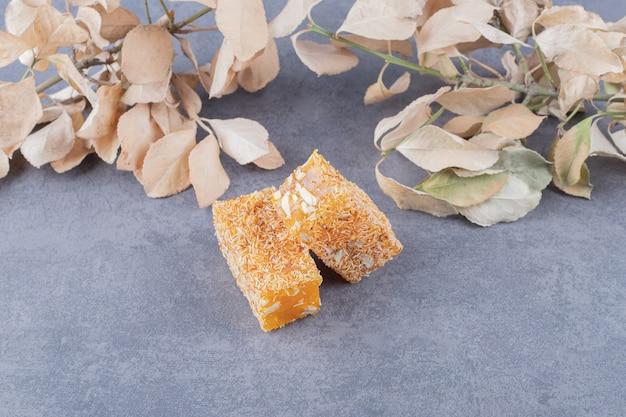 Gelber traditioneller türkischer genuss mit erdnüssen und dekorativen trockenen blättern.