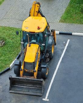 Gelber traktor bleibt auf parkplatz. schwere industriemaschinen. ansicht von oben.