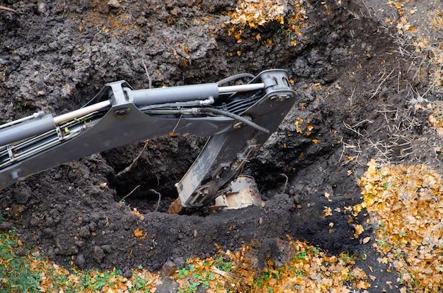 Gelber traktorbagger gräbt eine grube mit einem eimer, unfall. durchbruch im untergrund. herbst winter draufsicht
